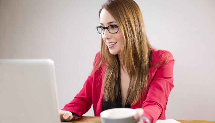 Woman smiling at laptop representing top candidate insights to improve recruitment