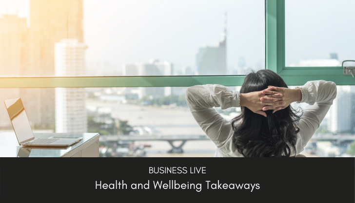 A woman sat with hands behind her head representing employee wellbeing initiatives