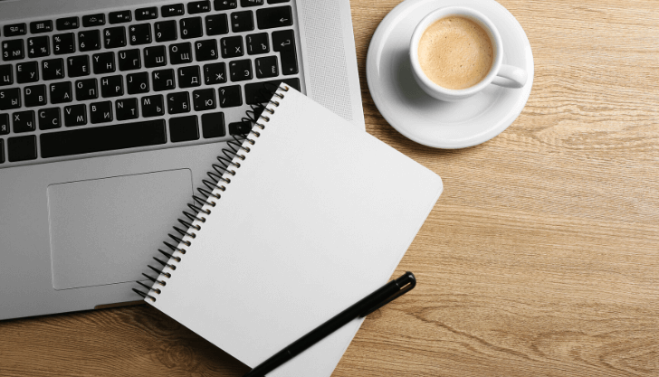 A notepad, laptop and coffee representing writing effective job advertisements