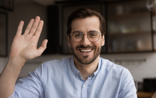 A man wearing glasses waving at the camera