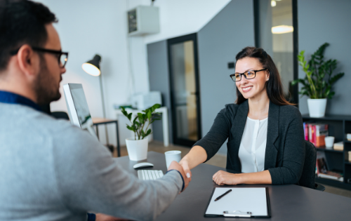 Woman shaking hands with a man at an interview