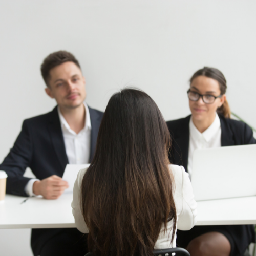 Two people interviewing a person