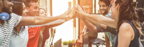 A positive teamwork culture high fiving in the workplace