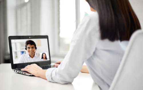 A woman on a video call with a man in a headset
