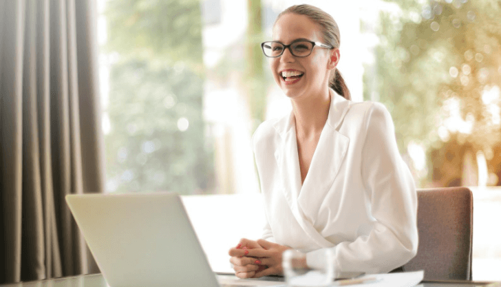 Woman smiling at a laptop representing how to create a culture of wellbeing