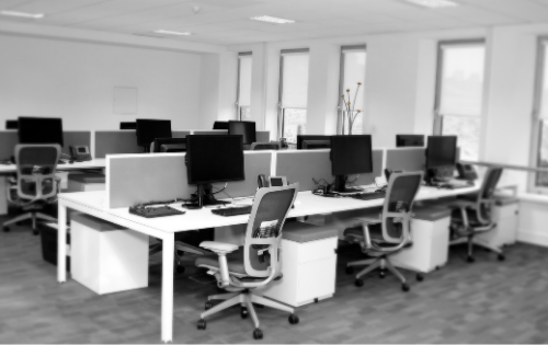 View of an office space with desks and chairs and computers