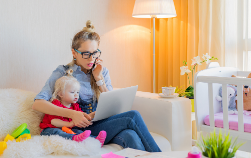 woman with a baby sat on a sofa on her phone