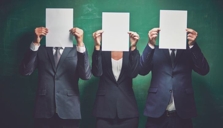 Three employees holding paper in front of their face to represent avoiding gender bias in job adverts